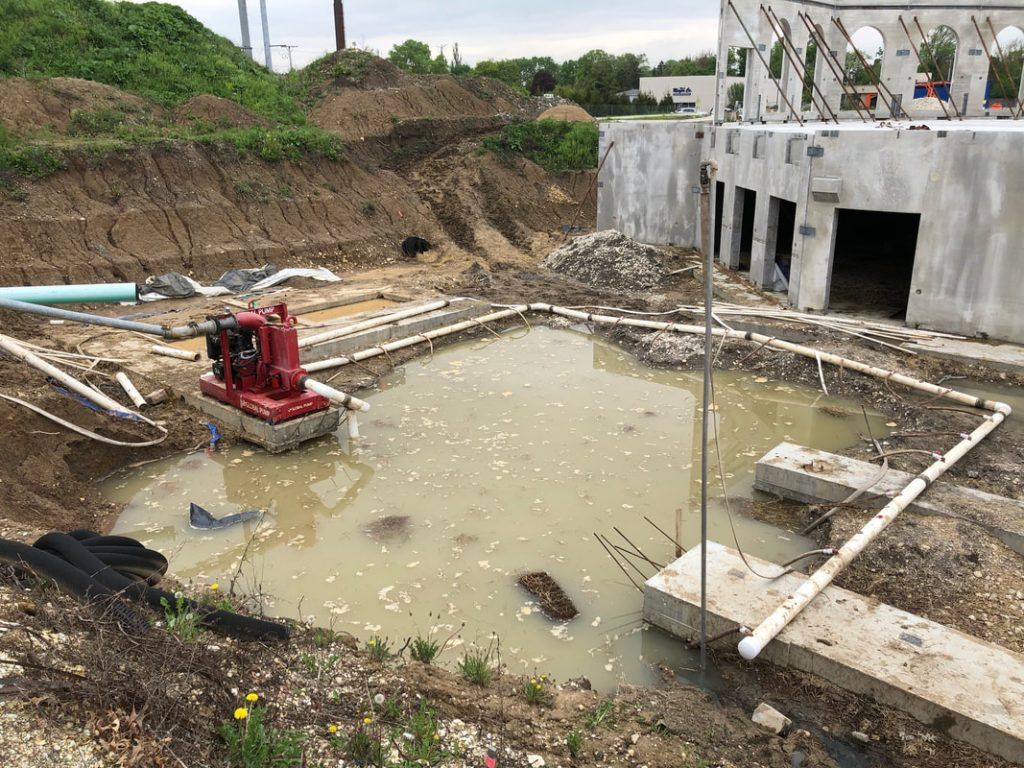 May 23, 2018: The struggle against underground water, compounded by heavy rains, continues. This has delayed the project, because the elevator pit and footing cannot be poured in this water.